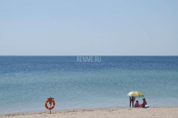 Отдыхающие в зонтиком на пляже в июле. Фото Заозёрного