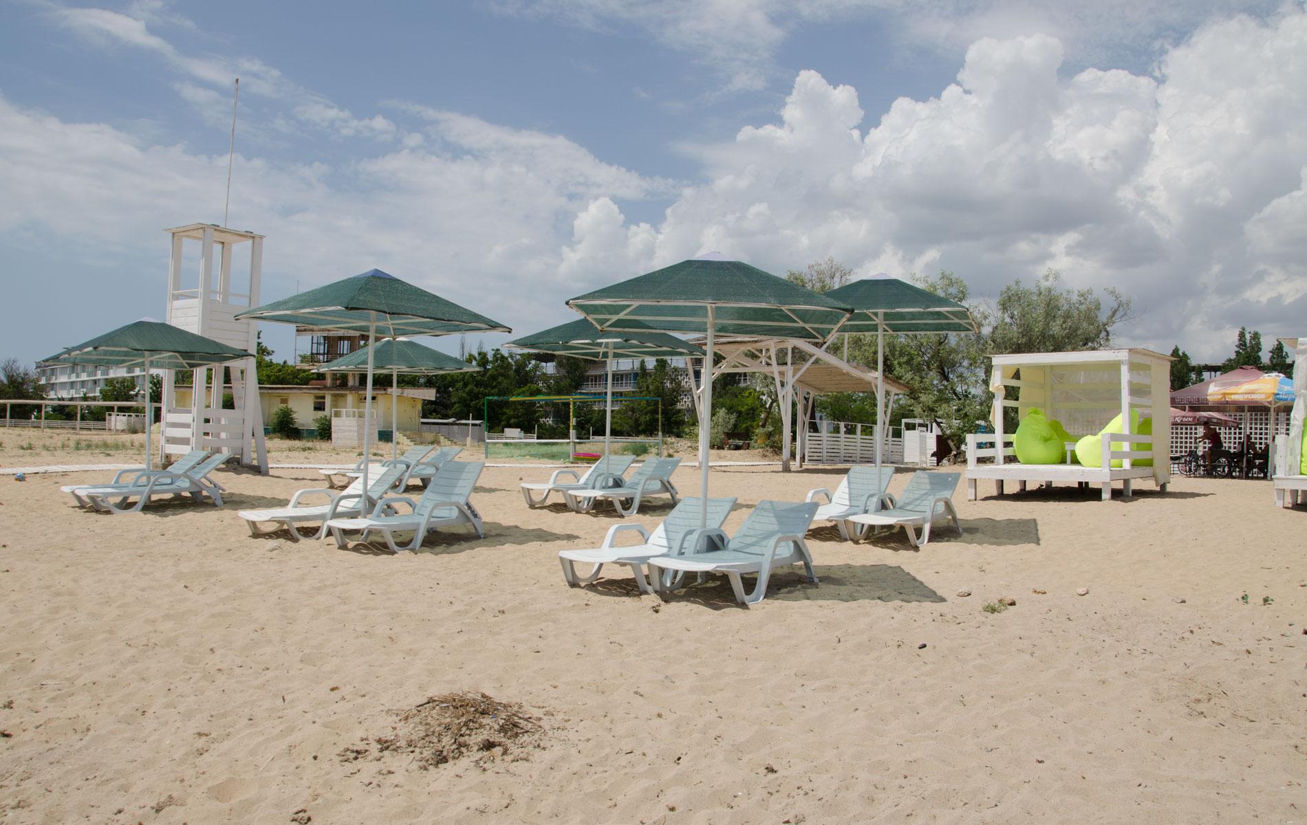 Зонтики и лежаки на пляже. Фото Заозёрного